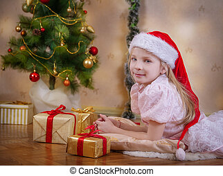 Girl in Santa hat dreaming under Christmas tree with gifts