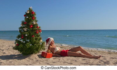 Girl in Santa hat enjoying Christmas vacation time on beach resort