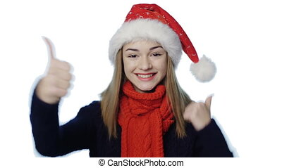 Girl in Santa hat gesturing thumb up
