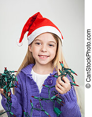 Girl In Santa Hat Holding Fairy Lights