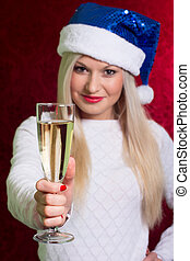 Girl in santa hat in white sweater smiling with a glass of champ