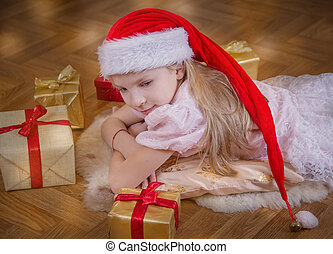 Girl in Santa hat lying among Christmas gifts