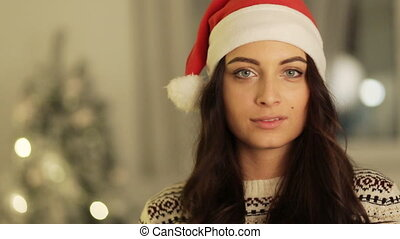 girl in santa hat portrait posing on tree lights background. , christmas holiday concept, happy and emotions