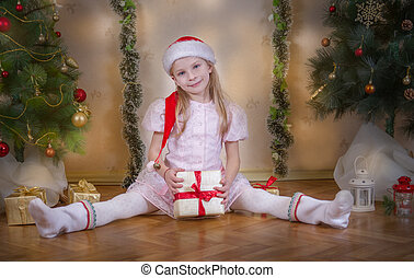 Girl in Santa hat sitting with gift among Christmas tree -...