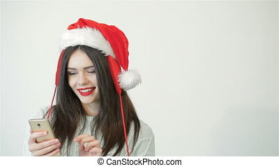 Girl in santa hat using a smartphone