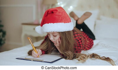Girl in Santa Hat Writes a Letter to Santa Claus