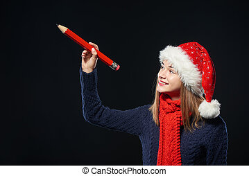 Girl in Santa hat writing on copy space