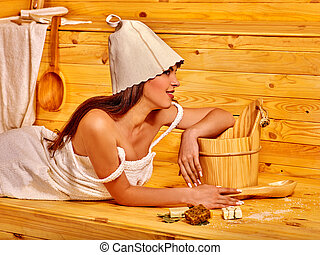Girl in sauna. - Woman wearing in cap for sauna relaxing...