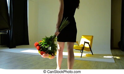 girl in sexy black dress goes to Studio with a bouquet of flowers in hand