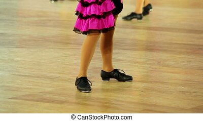 Girl in shoes with taps and pink skirt tap dance, only legs...