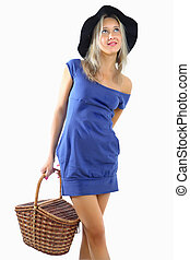 Girl in short blue dress and hat, holding a wicker basket.