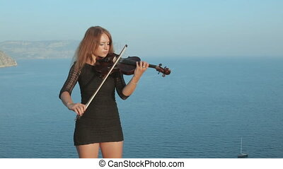 Girl in short dress standing on a rock near sea and playing the violin