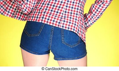 Girl in short jeans blue shorts. Close-up view from behind....