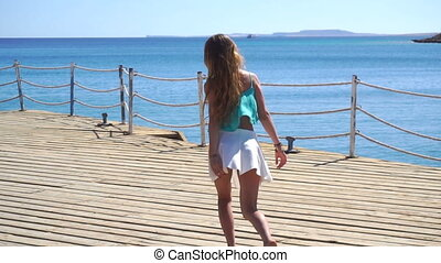 girl in skirt and with long hair running down the pier at sea in slow motion