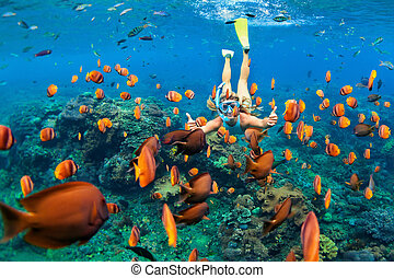 Girl in snorkeling mask dive underwater with coral reef...