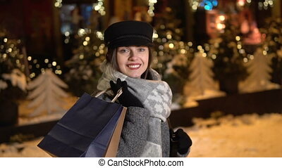 Girl in Snowy Street - Smiling beautiful girl with shopping...
