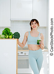 Girl in sports clothes standing in the kitchen, holding smoothie