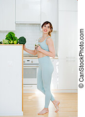 Girl in sports dress standing in the home kitchen, with green smoothie