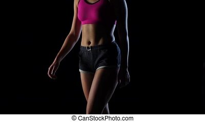 Girl in sports goes on a black background. Silhouette. Slow motion. Close up