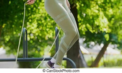 Girl in sports leggings jumping rope, close up