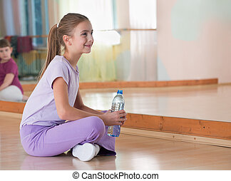 Girl in sportswear with bottle of water sits on the field at the gym in the mirror.