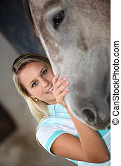 Girl in stable with horse