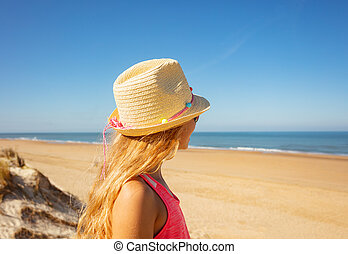 Girl in straw hat looks at sea view from behind
