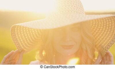 girl in straw hat posing at sunset
