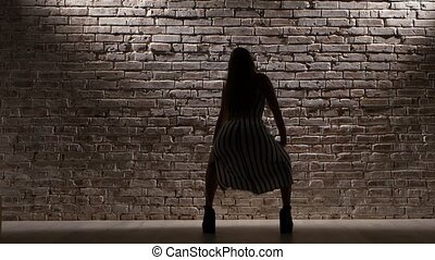 Girl in striped dress dancing against the light brick wall. Silhouette