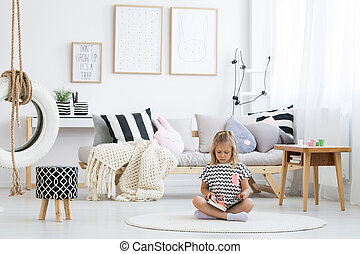 Girl in striped shirt reads book on white round carpet in...