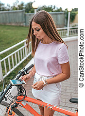 Girl in summer city in hand phone, choice of route, park bike. Online application for renting bicycles. Bike activation, nfs sensor. Building route on map smartphone, online app to Internet.