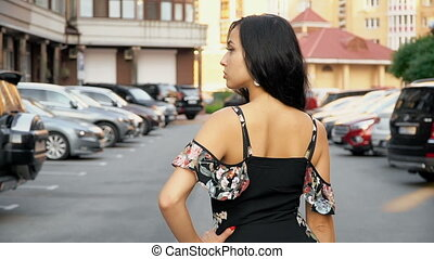 Brunette in summer dress posing in the parking lot
