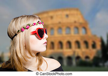 Girl in sunglasses and wreath on Coliseum blurred background