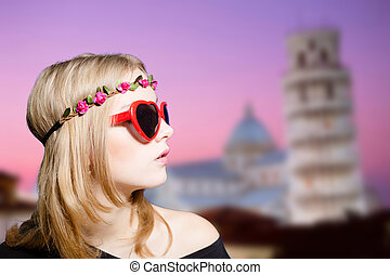 Girl in sunglasses and wreath on Pisa tower blurred background