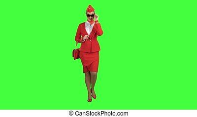 Girl in sunglasses is walking. Green screen