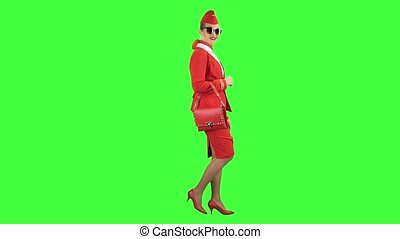 Girl in sunglasses is walking. Green screen. Side view