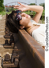 Girl in sunglasses laying carelessly on the railroad