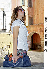 Girl in sunglasses on a background of the old walls