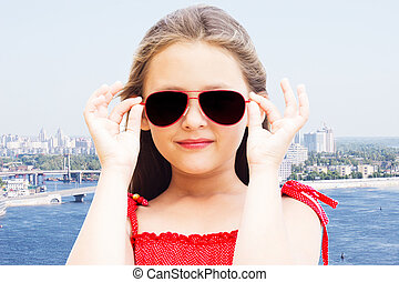 girl in sunglasses on background of the city