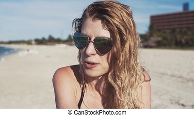 girl in sunglasses on the beach, smiling