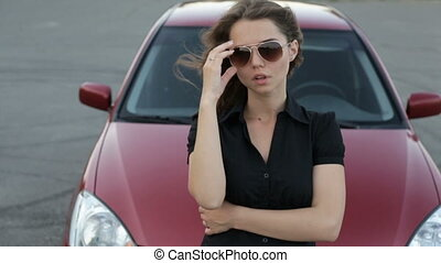 Girl in sunglasses posing against red car background