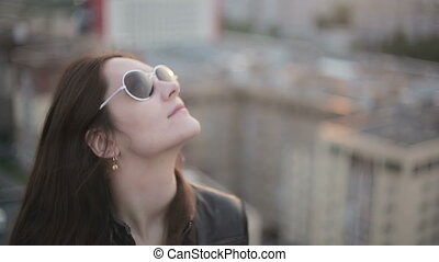 Girl in sunglasses standing on the roof at sunset