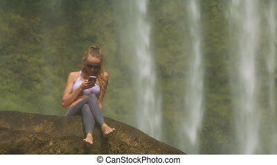 Girl in Sunglasses Texts Message against Waterfall