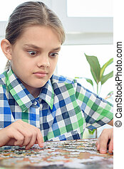 Girl in surprise looks at the puzzle on the table