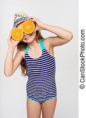Girl in swimsuit making fake eyeglasses with oranges -...
