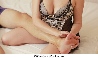 girl in the bedroom makes a foot massage man. girl makes a...