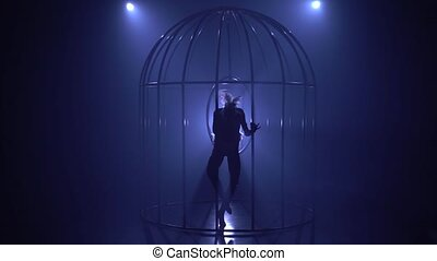 Girl in the cage performs gymnastic stunts in a dark room. Blue smoke background. Silhouette