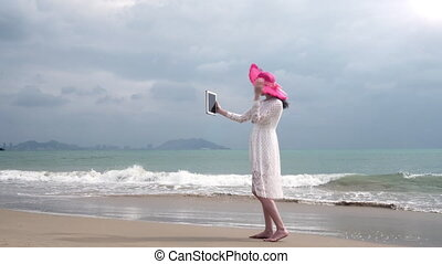 Girl in the color hat with ipad on the beach