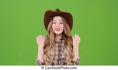Girl in the cowboy hat rejoices at the victory. Green screen...