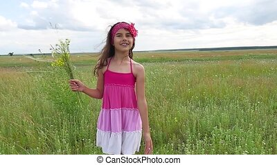 Girl in the field. Little girl teenager walking on field with flowers lifestyle on nature.
